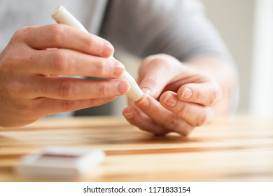 Diabetes and healthcare concept - a woman uses a blood lancet to take a blood sample for measuring blood sugar levels at home.