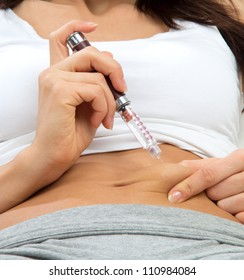 Diabetes woman patient make an abdomen subcutaneous syringe injection with needle on a sofa at home