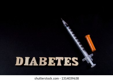 Diabetes wooden letters and insulin syringe on black background
