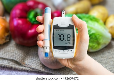 Diabetic diet and diabetes concept. Hand holds glucometer. Vegetables in background.