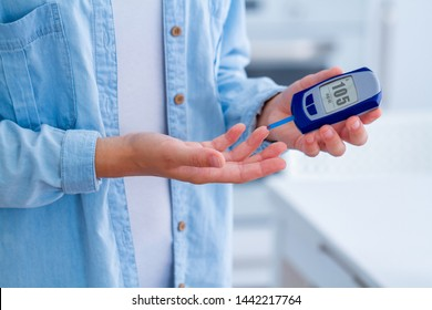 A diabetic patient measures blood glucose with a glucose meter at home. Diabetes woman control and analyze glucose level blood