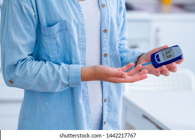 A diabetic patient measures blood glucose with a glucose meter at home. Woman having diabetes, control and analyze glucose level