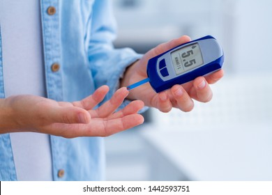 A diabetic patient measures blood glucose with a glucose meter at home. Woman control her diabetes