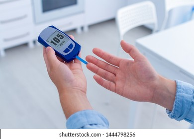 A diabetic patient measures blood glucose with a glucose meter at home. Woman having diabetes, control and analyze glucose blood level
