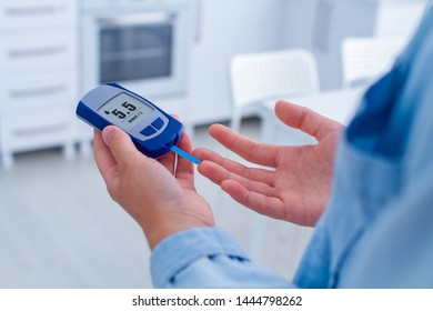 A diabetic patient measures blood glucose with a glucose meter at home. Woman having diabetes, control glucose blood level