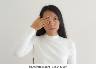 diabetic retinopathy in asian women and she is touching eye, symptoms of blurred vision and eye floaters or transparent and colorless spots.