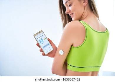 Diabetics patient checking glucose level with a remote sensor and smartphone. Continuous monitoring glucose levels without blood using digital glucose meter. Health care