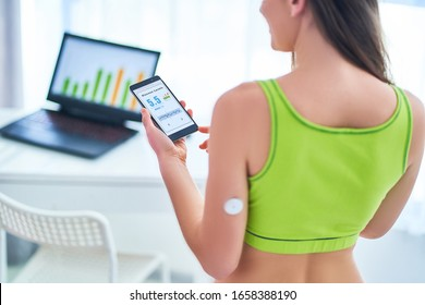 Diabetics patient control and checking glucose level with a remote sensor and mobile phone. Monitoring glucose levels using digital glucose meter. Medical modern technology in diabetes treatment