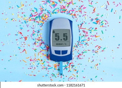 Diabets. Glucose meter and sweet powder on a blue background. World diabetes day, diabetes concept