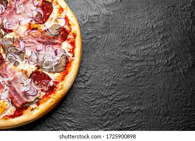 DIABLO pizza on a black background, tomato-based Pizza with mozzarella, veal, bacon, Napoli salami, onion and chili pepper on a wooden stand