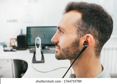 Diagnosis of hearing impairment, tympanometry, hearing test. A man during a hearing diagnostic procedure, and a special earphone in his ear.