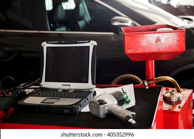 Diagnostic machine tools ready to be used with car in background