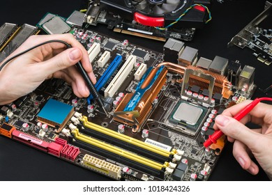 Diagnostics of the old motherboard with a voltmeter on a black table. Workplace repairman with special tools and a disassembled computer