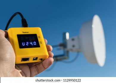 Diagnostics of outdoor wireless wifi receiver. Detail of specialist's hand holding a measuring device to check a power supply voltage of the wi-fi access point for transmission of internet signal.