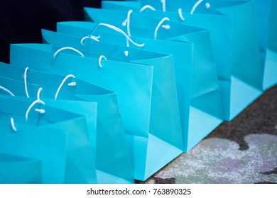 Diagonal close up on a row of formal robin egg blue paper bags with white string handles from a luxury jewelry store