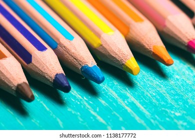 diagonal of colored pencils on a blue wooden background