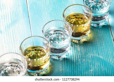 diagonal of glasses with liquor of different colors, vodka and tequila on the table