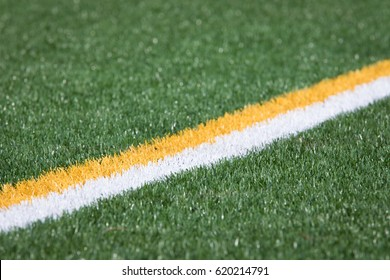 Diagonal parallel yellow and white boundary stripe painted on artificial green grass turf athletic field