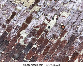 Diagonal red bricks, cement, and white paint textured background with copy space.