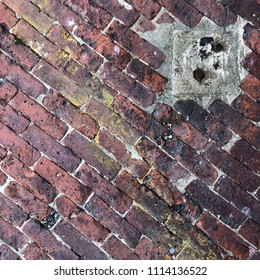 Diagonal red bricks, cement, yellow paint, and rusty metal textured background with square copy space.