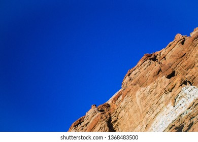 Diagonal rock angle of orange sedimentary cliff face above the mojave Desert in California.