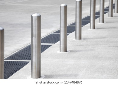 Diagonal row of chrome metal bollard poles along a concrete sidewalk, with space for text on the right