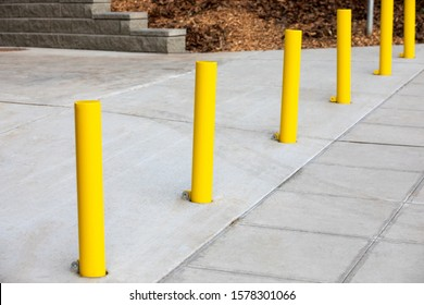 Diagonal row of yellow metal bollard poles along a concrete sidewalk, with space for text on the right