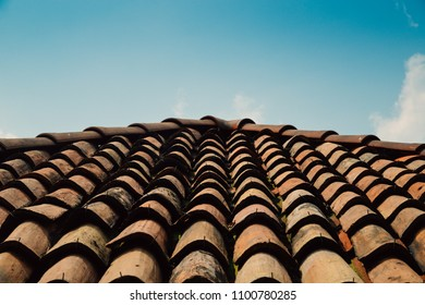 Diagonal rows of orange clay roof tiles on Mediterranean town with blue sky copy space
