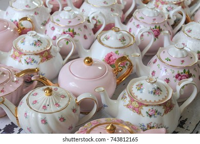 Diagonal rows of vintage pink, white, gold and floral design bone china teapots - high tea party