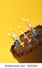 A diagonal shot of birthday or anniversary cake with lit candles.