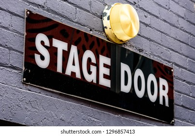 A diagonal 'Stage Door' sign with white on black lettering, on a brick wall and a lamp above