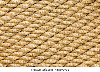 Diagonal strands of a new thick sisal and hemp rope with twisted braided fibers in a full frame close up background texture