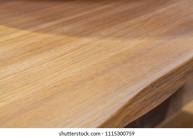 Diagonal upper view down on flat wooden board with wood texture and complex shape of board's edge lit with artificial light