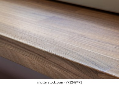 Diagonal view down on flat wooden board (windowsill) with wood texture and board's edge lit with natural light, FOCUS ON CENTER OF BOARD'S EDGE