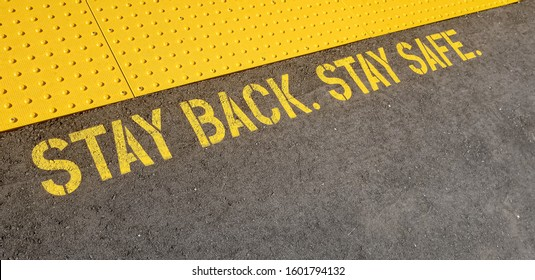 diagonal view yellow sign at train station asking people to stay back, stay safe, on concrete floor