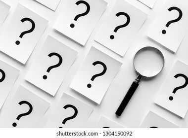 Diagonally orientated question marks printed on white paper cards and a magnifying glass in a neat background pattern viewed from overhead