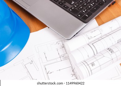 Diagrams or electrical construction drawings with laptop and protective blue helmet for engineer jobs, technology concept