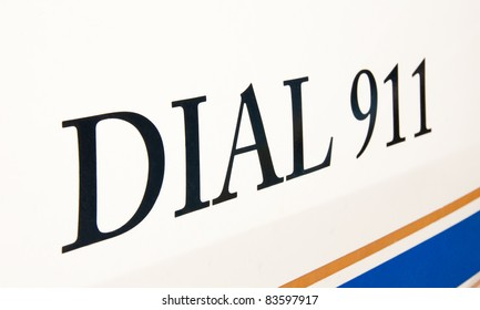 Dial 911 text on side of a police car