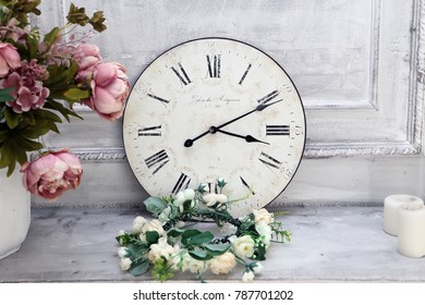 The dial of the watch and a bouquet of flowers on the white dresser