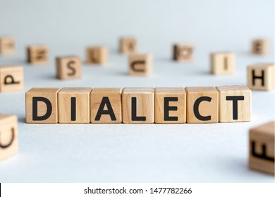 dialect - word from wooden blocks with letters, form of a language dialect concept, random letters around, white  background
