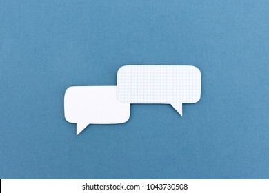Dialog with two blank white speech bubbles cut from paper