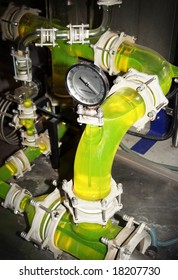 Dials, joints and a green liquid in see through pipework