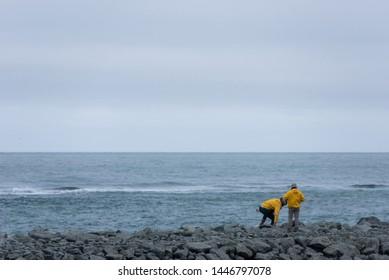 DIAMOND BEACH, JOKULSARLON, ICELAND - MAY 22, 2019: Tourists admiring and photographing the Atlantic ocean coast in Jokulsarlon