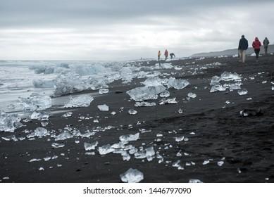 DIAMOND BEACH, JOKULSARLON, ICELAND - MAY 22, 2019: Tourists admiring and photographing the melting icebergs on the Atlantic ocean coast in Jokulsarlon