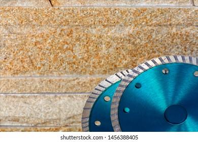 Diamond blades for bricks, stones and granitans against an orange-golden sandstone wall.