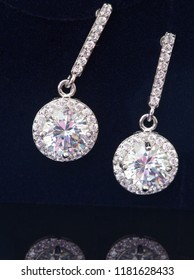 Diamond earrings jewelry, luxury silver earrings with diamond, sapphires in black background.