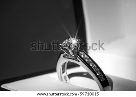A diamond engagement ring in a box with glint/reflection.
