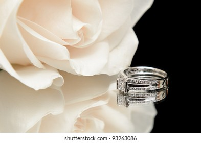 A diamond engagement ring with a white rose, shot with a reflection on a black background.