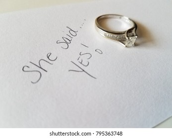 Diamond engagement  wedding ring displayed   and isolated white background with a note card that reads She Said Yes!