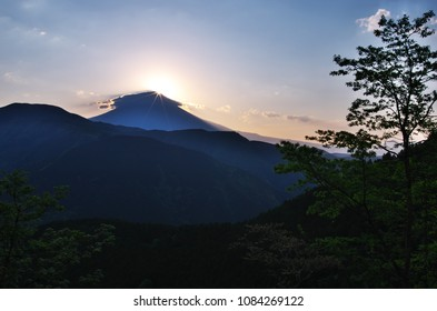 "Diamond Fuji ascending from ""Umbrella cloud over Mt. Fuji"" seen from SANO mountain Pass, Yamanashi prefecture, Japan. Diamond Fuji is View of the sunrise at the summit of Mt. Fuji."